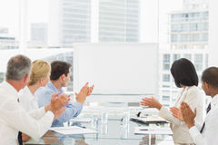 Business people applauding blank whiteboard in conference room Royalty Free Stock Photos