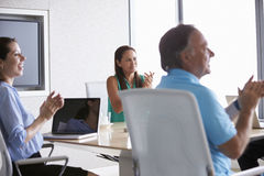 Business people Applauding Colleague In Boardroom Royalty Free Stock Photo