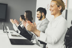 Business people applauding at conference. Young business people applauding at conference Royalty Free Stock Photo