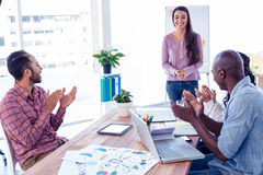 Business people applauding for female coworker Stock Image