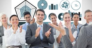 Business people applauding with graphs in background. Digital composite of Business people applauding with graphs in background Stock Photography