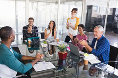 Business people applauding during meeting. Business people applauding while discussing at desk during meeting Stock Images