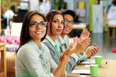 Business people applauding in a meeting. Happy business people applauding in a meeting. Business concept Stock Images