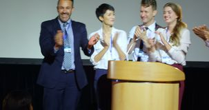 Business people applauding at podium on stage in auditorium 4k