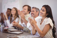 Business people applauding during presentation in office. Smiling business people applauding during presentation in office Stock Images