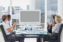 Business people applauding at a screen. During a video conference Royalty Free Stock Images