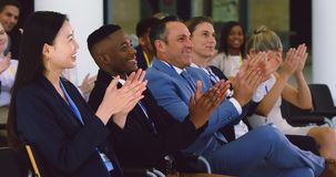 Business people applauding in a business seminar 4k. Side view of diverse business people applauding in a business seminar. They are attending a business seminar stock video