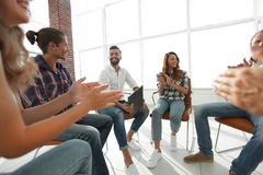 Business people are applauding. And smiling while sitting in circle in office Stock Photography