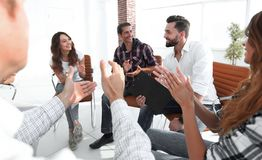 Business people are applauding. And smiling while sitting in circle in office royalty free stock image