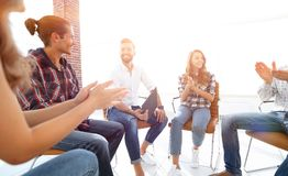 Business people are applauding. And smiling while sitting in circle in office royalty free stock images