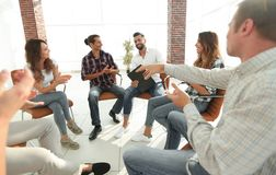 Business people are applauding. And smiling while sitting in circle in office royalty free stock photography