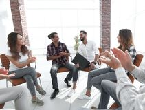 Business people are applauding. And smiling while sitting in circle in office stock images
