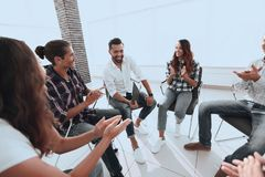 Business people are applauding. And smiling while sitting in circle in office royalty free stock photo