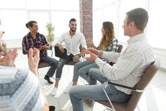 Business people are applauding. And smiling while sitting in circle in office stock photo