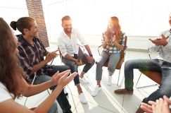 Business people are applauding. And smiling while sitting in circle in office royalty free stock photos