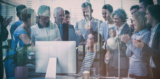Business people applauding their colleague presentation. In office seen through glass Stock Image