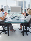 Business people applauding during a video conference. While they are sat in the boardroom Royalty Free Stock Image