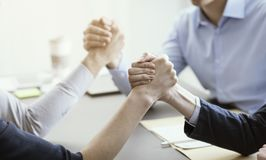 Business people arm wrestling in the office. Business people arm wrestling on the office desk, challenge and competition concept stock image