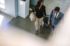Business people arriving at hotel with luggage. Business people with luggage walking together and chatting Stock Photography