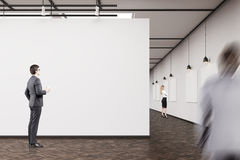Business people in an art gallery with dark wood floor. Businessman in dark suit is standing in an art gallery and looking at a picture. His colleague is going Stock Photo
