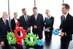 Business people assembling cogwheels Stock Photo