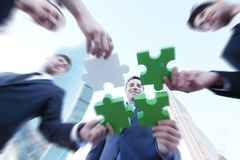 Business people assembling jigsaw puzzle royalty free stock photo