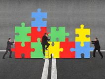 Business people assembling jigsaw puzzle Royalty Free Stock Photos