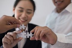 Business people assembling piece of puzzle together. co worker t royalty free stock image