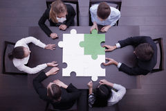 Business people assembling puzzle royalty free stock photo