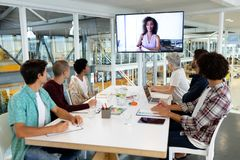 Business people attending video conference at conference room in a modern office. Rear view of diverse business people attending video conference at conference stock image