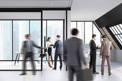 Business people in attic office. Business people are standing and walking in an attic office with glass walls and computer tables. 3d rendering Stock Photo