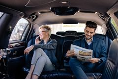 Business people at back seat of limo stock photo