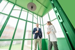Business people in the green hall Stock Images