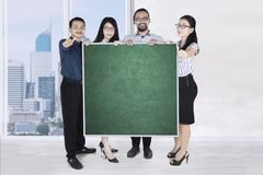 Business people with blackboard and thumb up Stock Images