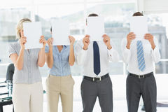 Business people with blank paper in front of faces in office Stock Photography