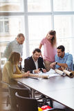 Business people with blueprint in meeting room Stock Images