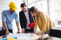 Business people with blueprint on table Stock Images
