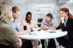 Business people board meeting in modern office. While sitting at round table Stock Image