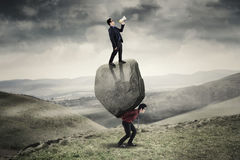 Business people with boulder in the hill. Image of young leader screaming with megaphone and standing on the stone while his employee lifting stone on the hill Stock Photography