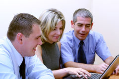 Business people - Browsing WWW. Three friends working on laptop. The main focus is on the man on the left Stock Image