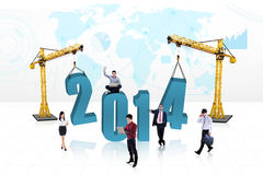 Business people building the new year 2014. Business people is building the new year 2014 with blue map background Stock Photo