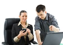 Business people. Businessman is showing something on computer to his colleague but she is not interested an looking her cellphone royalty free stock images