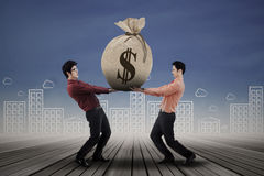 Business people carrying money bag. Two business people carrying a money bag with US dollar sign Stock Photography