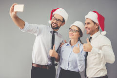 Business people celebrating Christmas. Happy business people in Santa hats are doing selfie and smiling while celebrating New Year, on gray background Stock Photography
