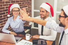 Business people celebrating Christmas. Happy business people in Santa hats are giving high five and smiling while celebrating New Year in office Royalty Free Stock Photos