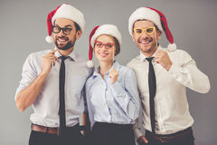 Business people celebrating Christmas. Happy business people in Santa hats are holding party props on sticks, looking at camera and smiling, on gray background Stock Photo