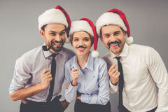 Business people celebrating Christmas. Happy business people in Santa hats are holding party props on sticks, looking at camera and smiling, on gray background Royalty Free Stock Image