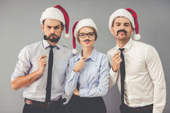 Business people celebrating Christmas. Happy business people in Santa hats are holding party props on sticks while celebrating New Year, on gray background Stock Photo
