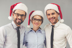 Business people celebrating Christmas. Happy business people in Santa hats are looking at camera and smiling, on gray background Royalty Free Stock Photos
