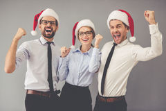 Business people celebrating Christmas. Happy business people in Santa hats are looking at camera and smiling while celebrating New Year, on gray background Royalty Free Stock Image